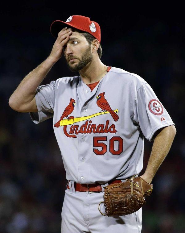 St. Louis Cardinals starting pitcher Adam Wainwright wipes