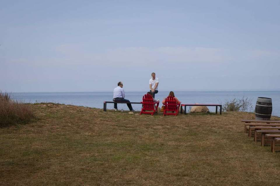 Adirondack chairs and benches overlook the Long Island