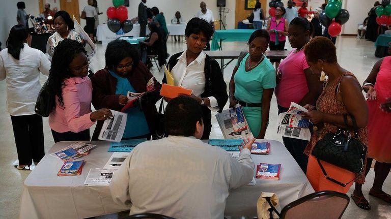 Job fair attendees speak with a recruiter in