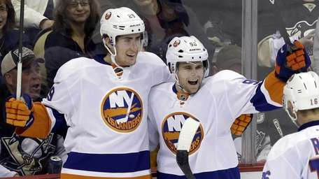 New York Islanders' Pierre-Marc Bouchard, right, celebrates his