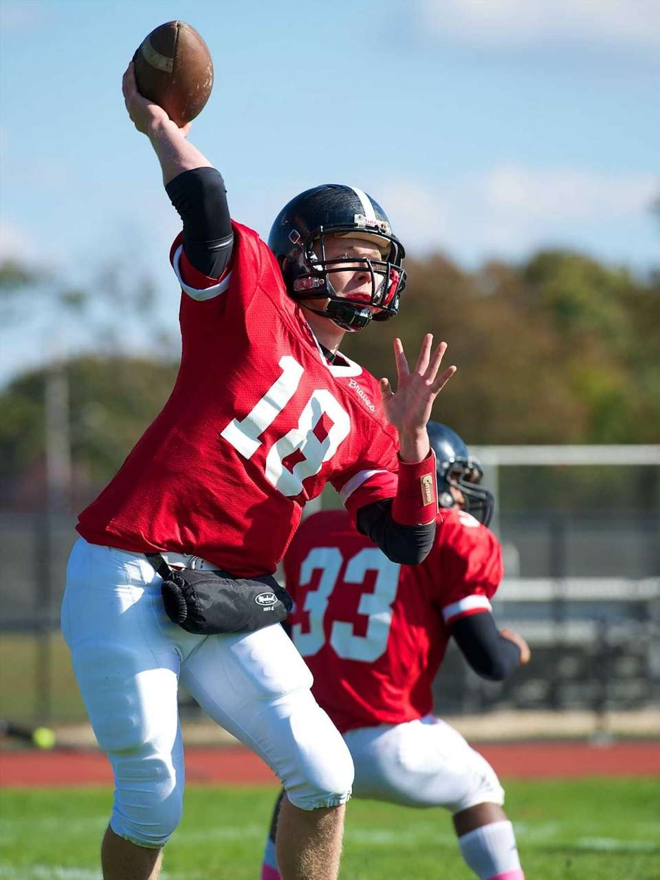 Syosset quarterback Joe Majoy throws out of his