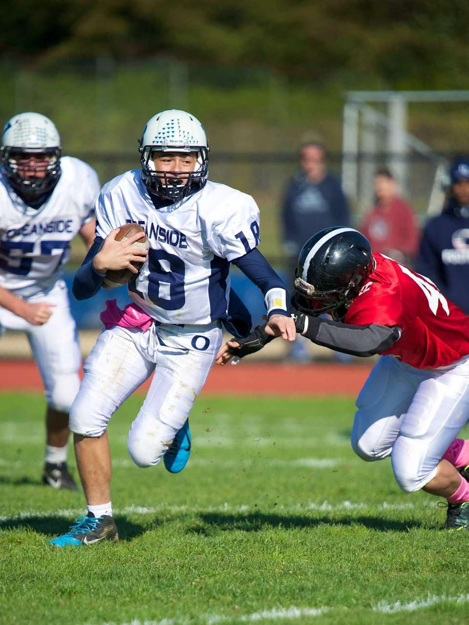 Oceanside quarterback Vincent Guarino runs past Syosset lineman