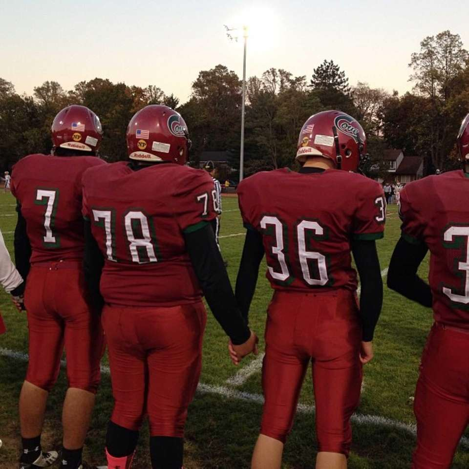 Glen Cove football players join hands before the