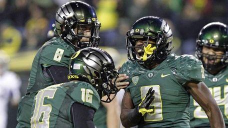 Oregon running back Byron Marshall, right, celebrates his