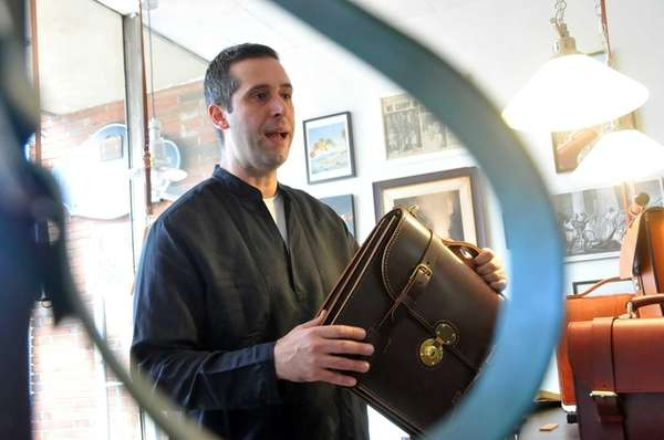 Joe Marcellino displays a finished handmade leather briefcase