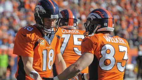 Denver Broncos quarterback Peyton Manning (18) congratulates wide