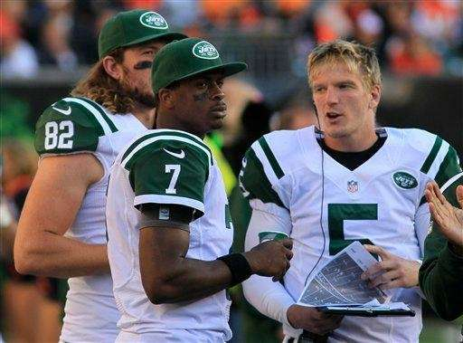 Geno Smith talks with Matt Simms (5) and