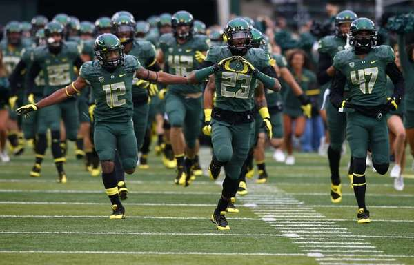 The Oregon Ducks run onto the field before