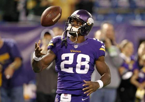 Minnesota Vikings running back Adrian Peterson tosses a