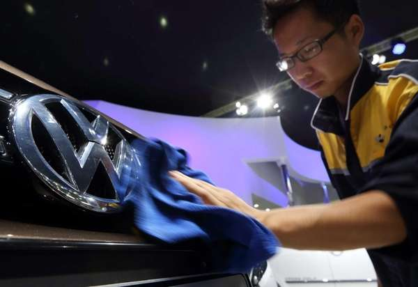 A worker wipes the Volkswagen logo on a