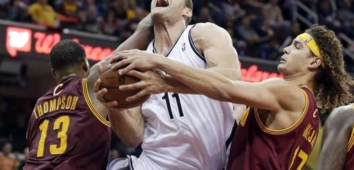 Brooklyn Nets' Brook Lopez is stopped by Cleveland
