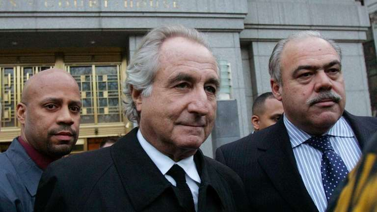 Bernard Madoff, center, walks out from federal court