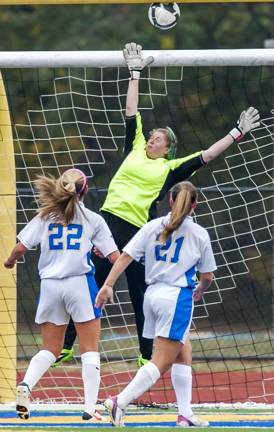 West Islip goalkeeper Megan Deak, center, goes up
