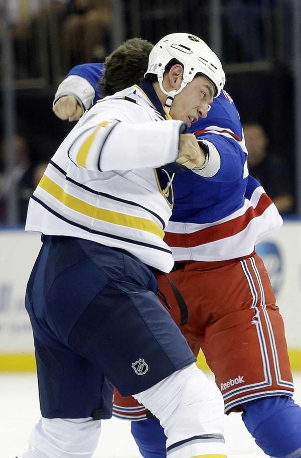 The Buffalo Sabres' Cody McCormick, left, fights with