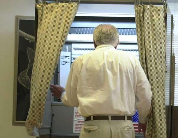 A voter entering a voting booth.