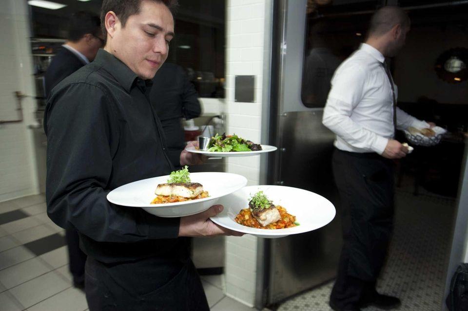 A waiter serves branzino filets at Revel in