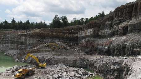 Miners using heavy equipment to dig wollastonite ore