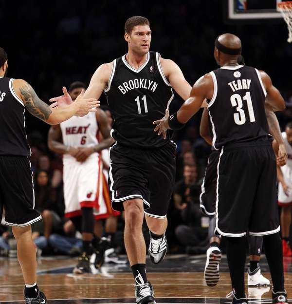 Nets' Brook Lopez is congratulated by teammates Deron