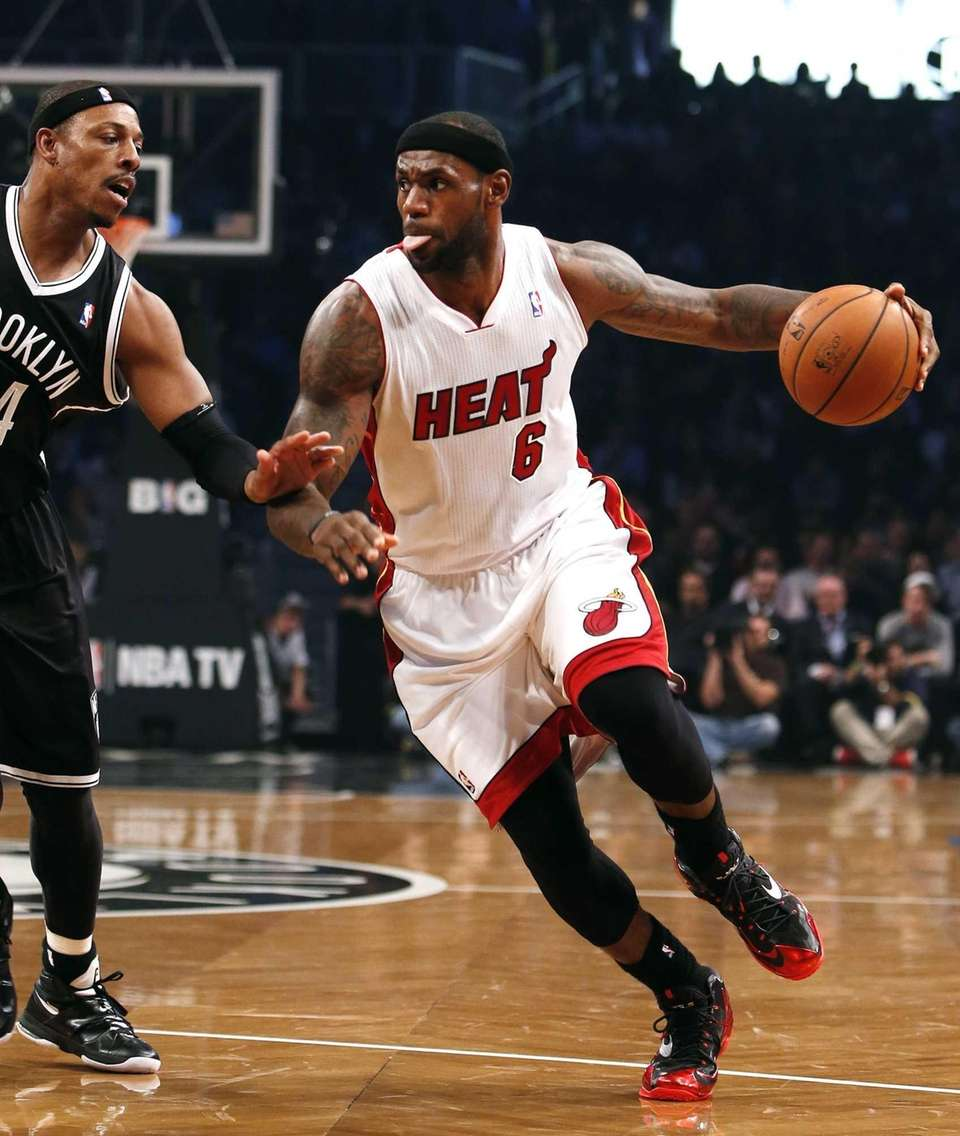 Miami Heat's LeBron James drives against Nets' Paul