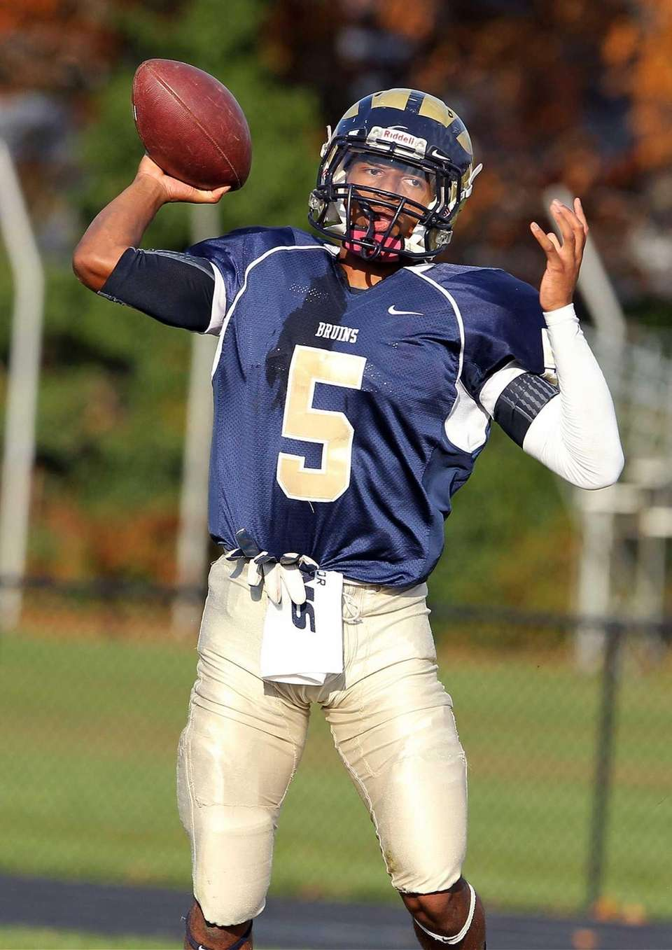 Baldwin's Tyler Warner looks to pass against Massapequa.