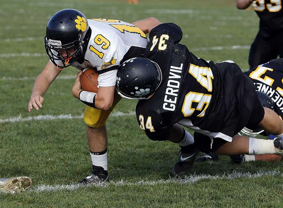 Commack quarterback Robert Paccione (19) dives into the