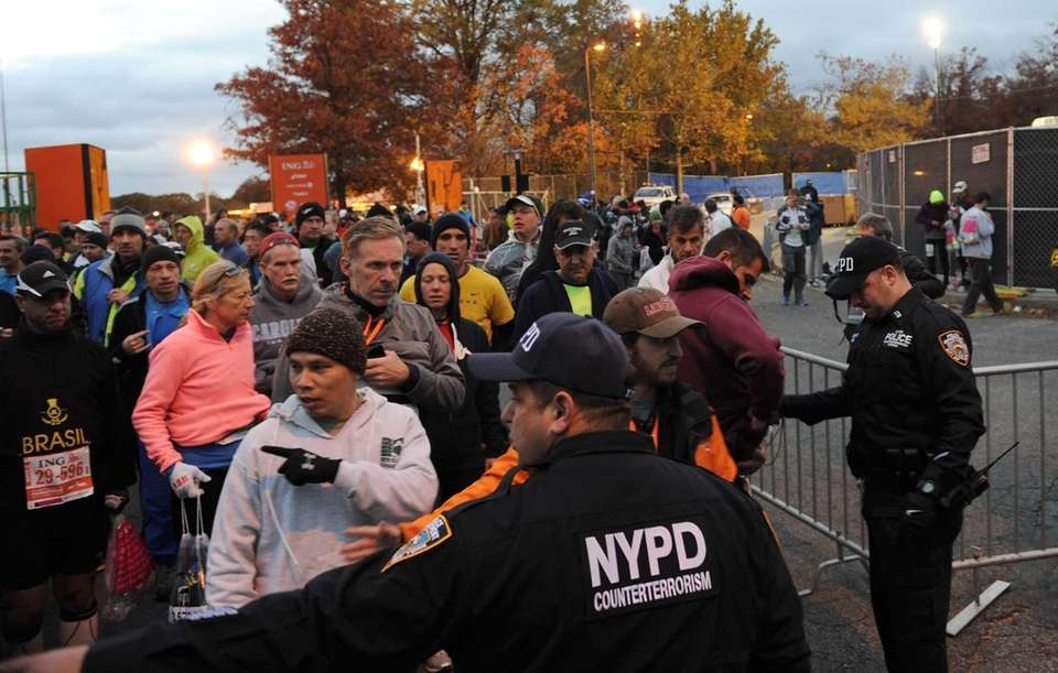 Runners file through a security checkpoint before the