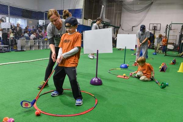 Aiden Lorenzo, 9, right, practices his golf swing