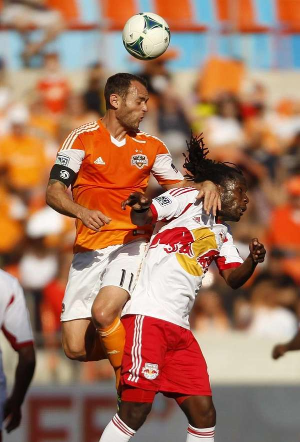 Houston Dynamo's Brad Davis, left, heads the ball