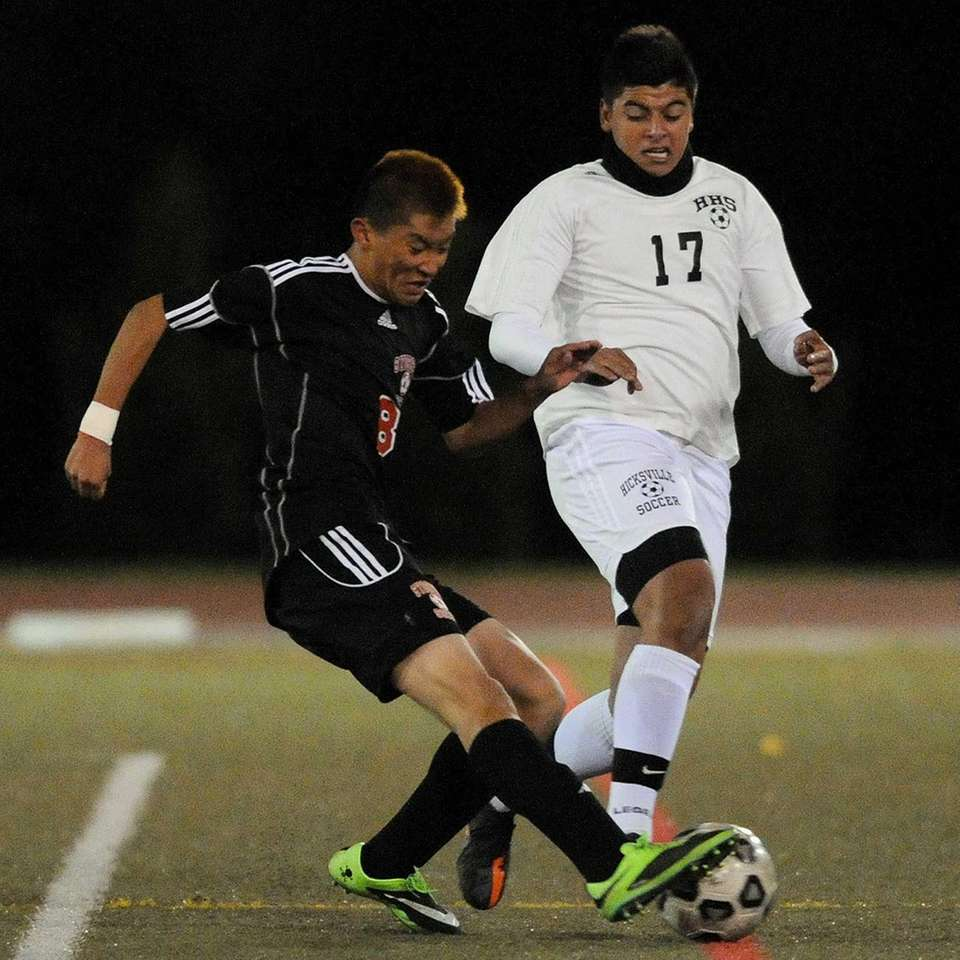Syosset's Justin Nho, left, challenges Hicksville's Charles Ortiz
