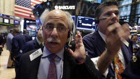 Trader Peter Tuchman, left, works on the floor