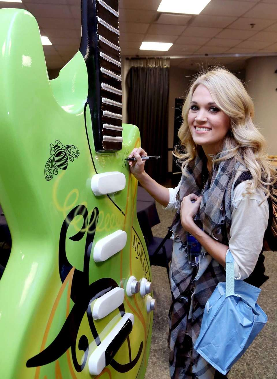 Carrie Underwood signs a giant Patron tequila guitar