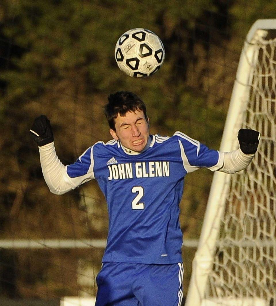 John Glenn's James Groark heads the ball against