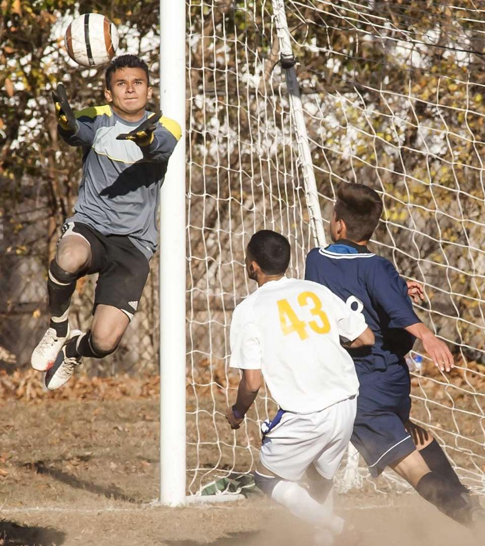 Central Islip goalkeeper Rene Melgar, left, goes up
