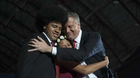 Mayor-elect Bill de Blasio hugs his daughter Chiara