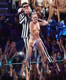 Miley Cyrus and Robin Thicke perform during