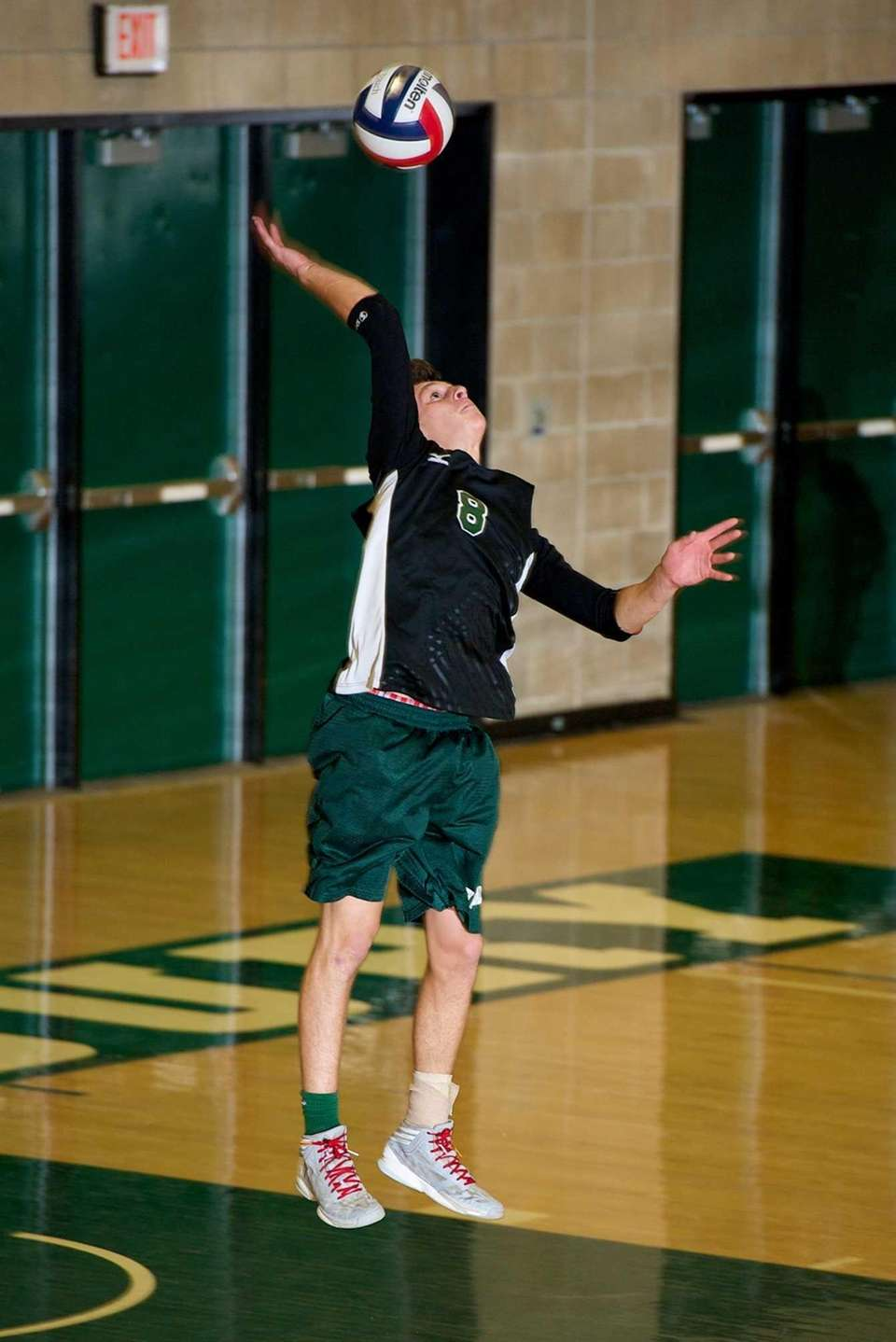 Bellmore JFK senior Justin Feigeles (8) serves the