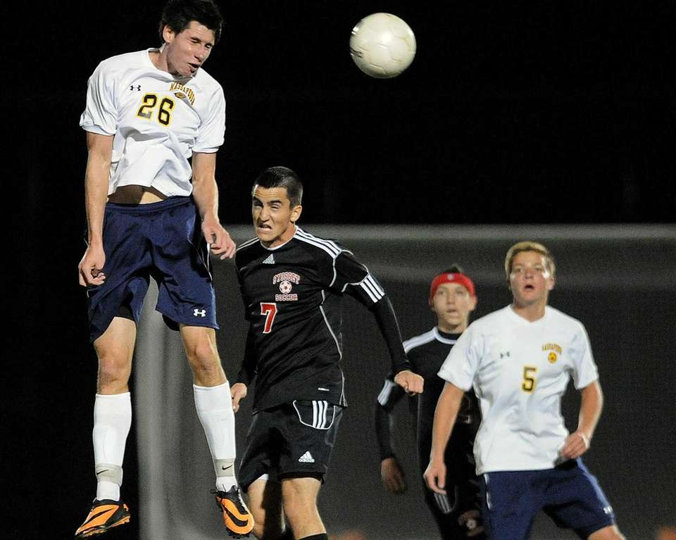 Massapequa's Sean Nealis, left, heads a ball away