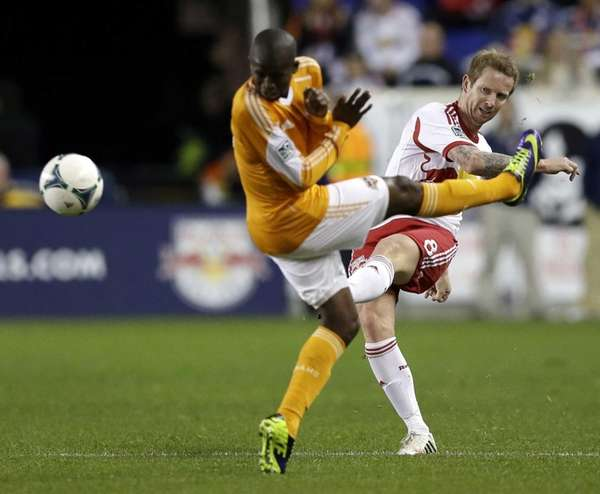 The Red Bulls' David Carney, right, kicks the