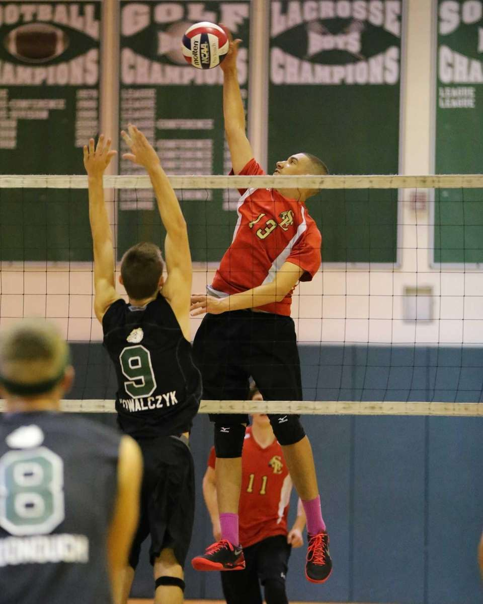 Sachem East outside hitter Ryan Cole spikes the