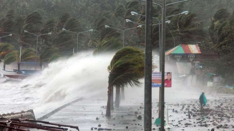 A resident walks past high waves pounding the