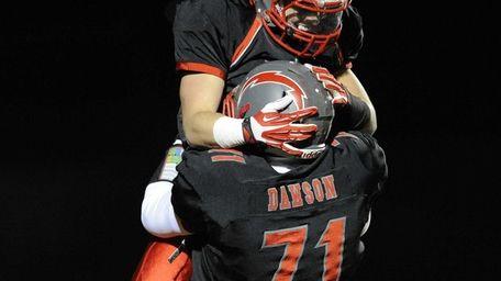 Connetquot's quarterback Michael Grimaldi, top, celebrates with Robert