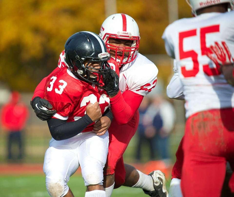 Syosset running back Brandon Nieves (33) is grabbed