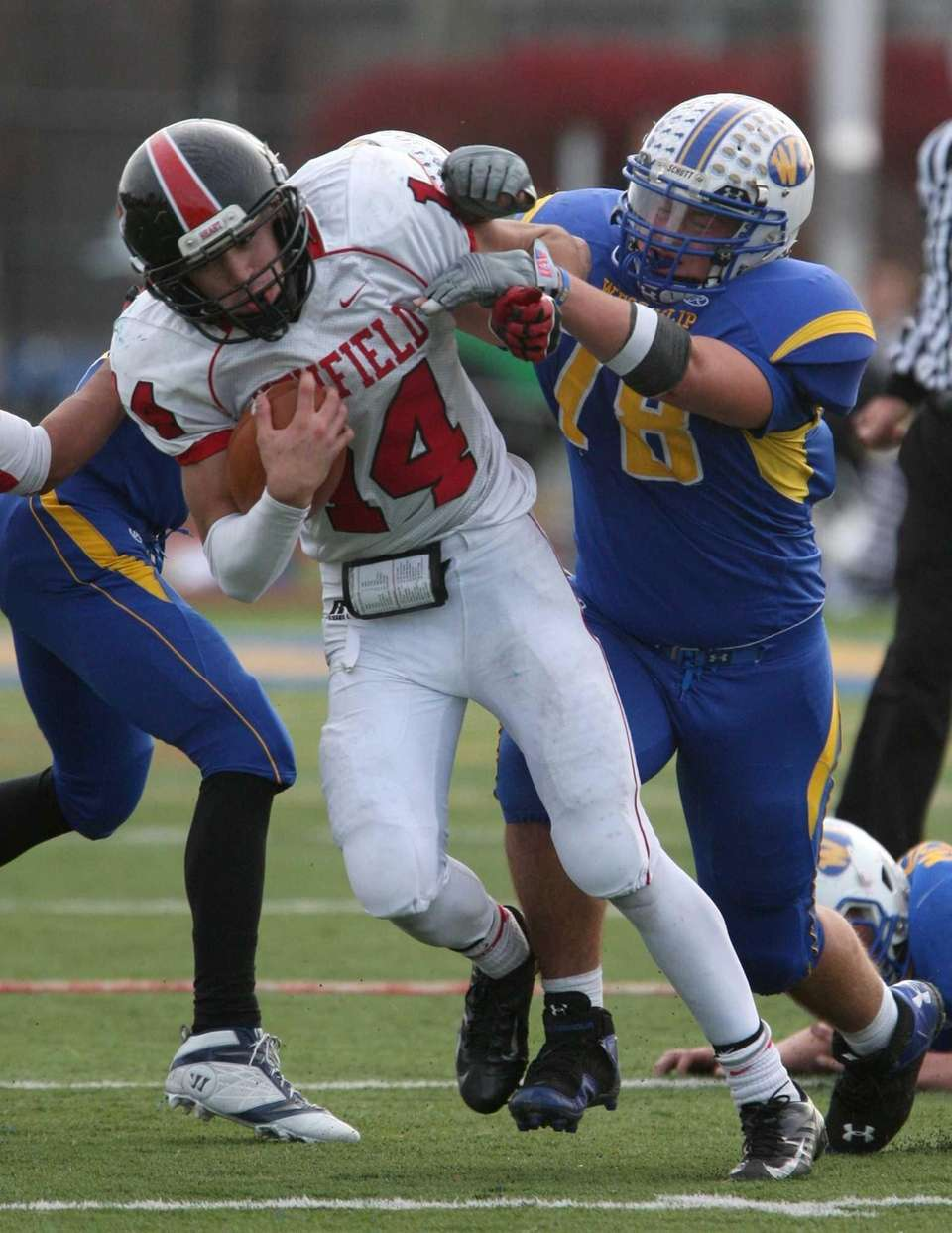 Dylan Harned of Newfield gets wrapped up by