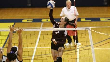 Kings Park's Joelle Goldstein spikes the ball against