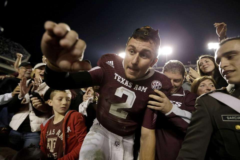 Texas A&M quarterback Johnny Manziel crawls out of