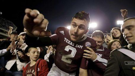 Texas A&M quarterback Johnny Manziel crawls out of
