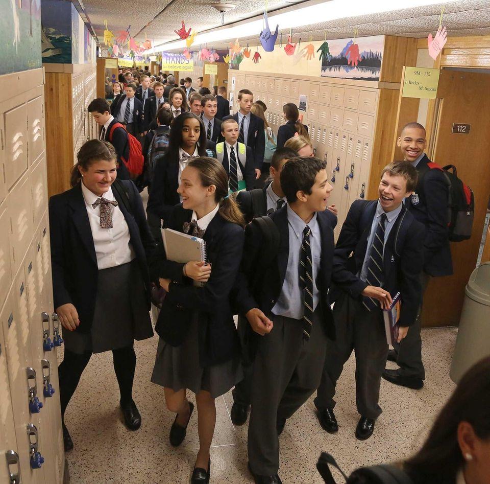 Catholic high school kids walk through the hallway.
