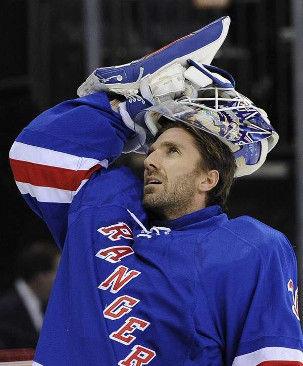 Rangers goalie Henrik Lundqvist puts on his helmet