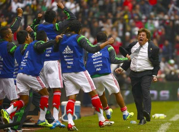 Mexican players celebrate a goal with coach Miguel