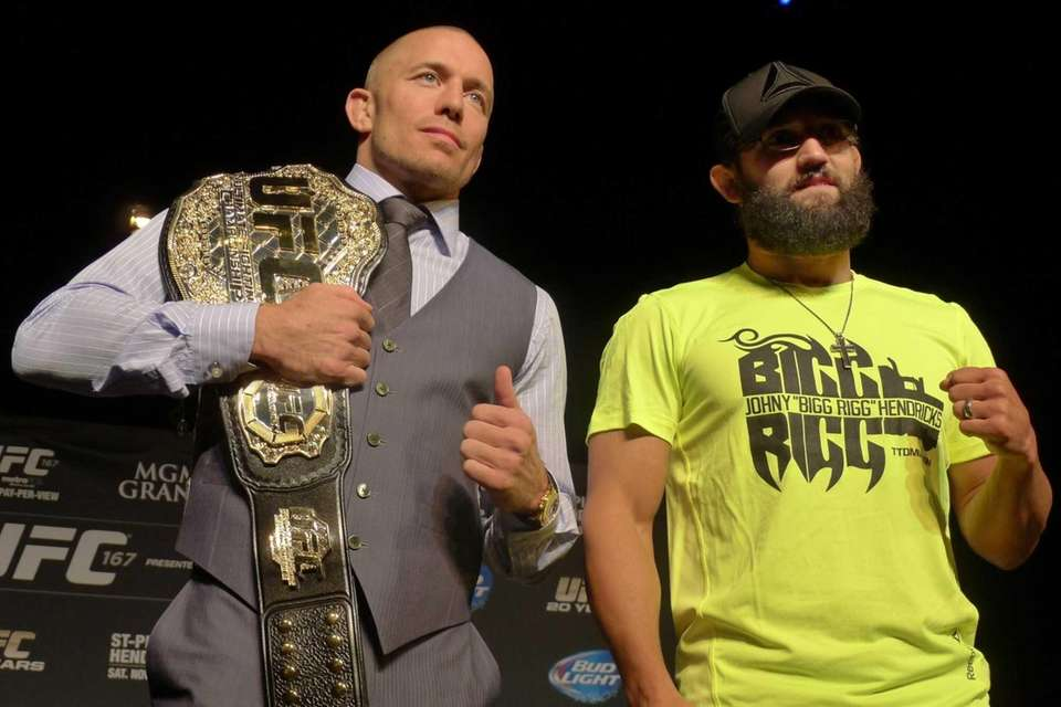 UFC welterweight champion Georges St. Pierre, left, poses